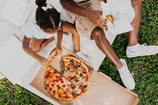 A family having a picnic and eating a box of pizza together