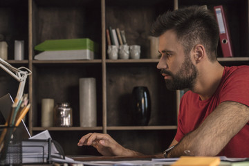 Young businessman sitting behind desk and send emails using laptop