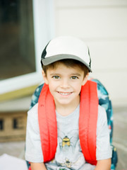 boy in backpack looking up at camera