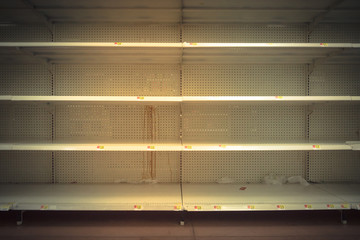 Empty shelves in store in Humble, Texas USA. Supermarket with empty shelves for goods. Vintage tone.