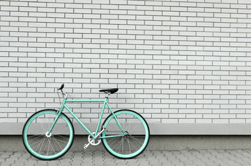 Spoed Foto op Canvas Fiets Teal bicycle next to white brick wall, copy space, no people