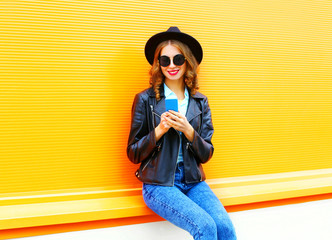 Fashion smiling woman is using smartphone in black rock jacket on a colorful orange background