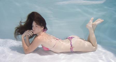 Woman wearing a bikini swimsuit holding her breathe underwater.
