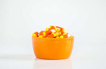 candy corn in an orange bowl isolated on white