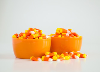 candy corn in 2 overflowing orange bowls isolated on white