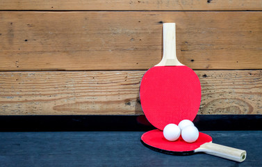 2 red ping pong paddles and 3 white ping pong balls on a black shelf against a wooden wall with copy space