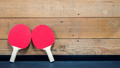 2 red ping pong paddles leaning against a wooden wall with copy space