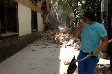 A man reacts near a damaged building after an earthquake hit Mexico City, Mexico