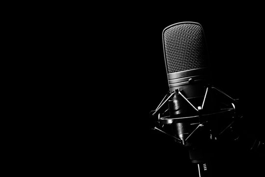 studio condenser microphone, isolated on black. copy space on left
