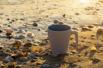 White coffee mug on the beach.