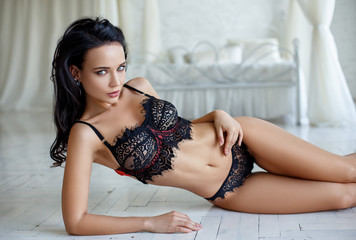 Beautiful woman in a sexy black lingerie in a bedroom
