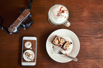 View from above. Coffee in white cup and cell phone with croissant, cake, marshmallows on the wooden background