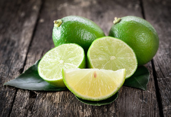 Fresh ripe limes on wooden background.