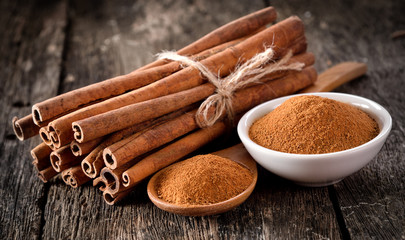 Photo sur Toile Condiment Cinnamon powder on table wooden