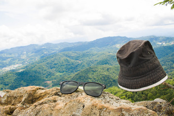 The old sunglasses , placed on the stone.The background is a mountain and the sky