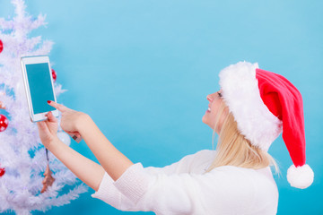 Woman in Santa hat sitting holding tablet