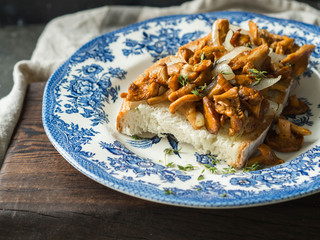 Big toast with fried chanterelles on an old blue plate on a dark background. season food