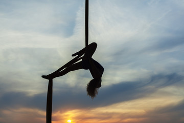 Woman's equilibrist does tricks high in the sky in the setting sun. Only the contours of the athlete.