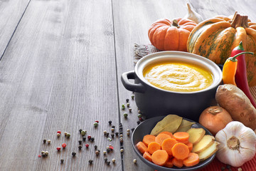 Pumpkin, carrot and ginger creme soup in a dark ceramic pan on the wooden table