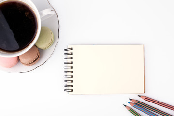 Free space for text, marketing and business information. Cake macaron and cap of coffee, notebook and colored pencils on a white background