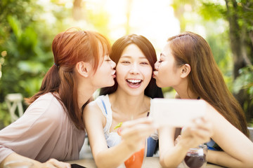 Group of friends taking selfie in garden restaurant