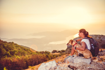 Woman with a dog on a mountain top