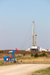 pump jack and oil drilling rig in the oilfield