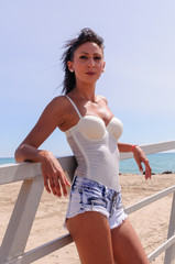 young and slim woman with white bathing suit and short cowboy pants on the beach