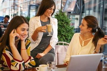 Three young women having conversation in cafe and using laptop.