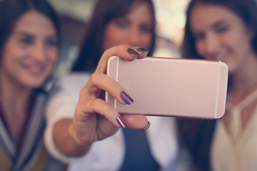 Three young women taking selfie together outdoors. Close up.