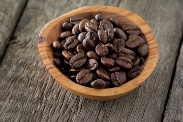 Coffee beans in wooden bowl on wooden background. Selective focus.