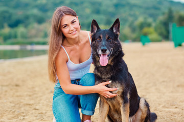 Girl with a dog in the park. German Shepherd with a woman in the nature.