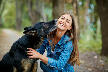 Portrait of a young girl with a dog hugging in the park. German shepherd with a woman.
