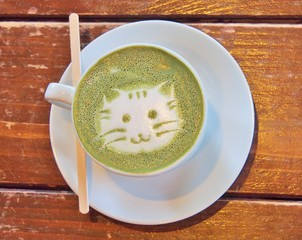 Matcha green tea latte with latte art 'Cat face' in the white cup with coffee stick on the wooden table.