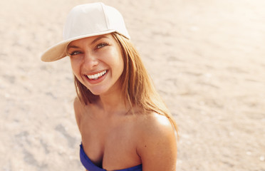 Portrait of a young girl at the beach./ Girl with  hat smiling and locking at the camera. Young girl smiling on the beach.
