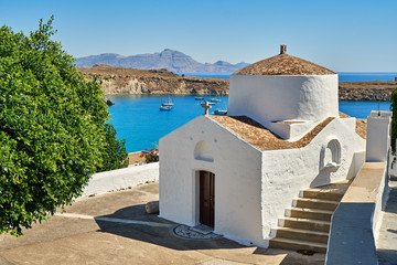 Fotobehang Cyprus White chapel. Chapel of Saint George Pahimahiotis, Lindos, Rhodes, Greece. Small building of Christian church located on embankment of calm blue sea on sunny day in coastal town