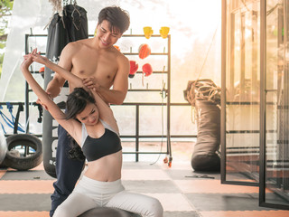 The acting set-up of the exercise concept. The young couple, man and woman exercising together at the gym.