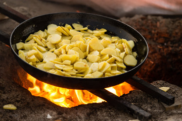 Potatoes fried in a frying pan in the open air
