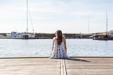 Young woman sitting on wood pier in harbor, alone, looking at horizont