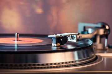 Vinyl record player, bright lights disco-bokeh. Needle on vinyl record.