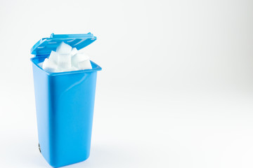 Blue trash can full of sugar cubes, white background