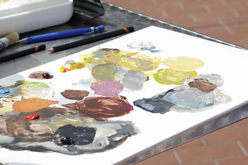 Art palette with oil paints and a brushes on a table