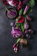 Assortment raw organic of purple vegetables mini eggplants, spring onion, beetroot, radicchio salad, plums, kohlrabi, flower salt over dark metal background. Top view with space
