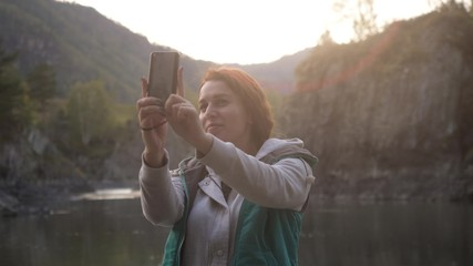 Young woman is taking pictures on the phone against the background of big mountains and the green mountain river. selfie or self-portrait on a smartphone