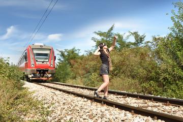 Woman taking dangerous selfie on railway track, train coming