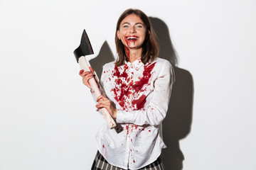 Happy mad zombie woman holding an axe
