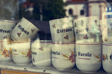 Coffee mugs behind a shop window.