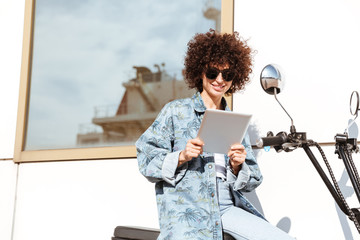 Happy young woman in sunglasses using tablet computer