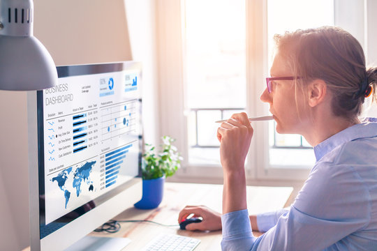 Businesswoman using business analytics or intelligence dashboard on computer screen