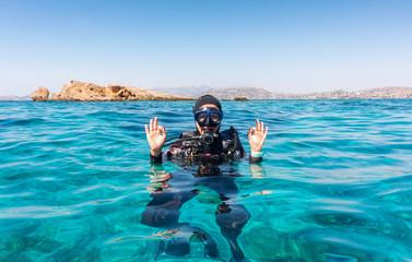 Canvas Prints Diving Weibliche Taucherin gibt das OK Zeichen an der Wasseroberfläche